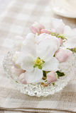 Table decoration of blooming apple tree flowers in crystal bowl Stock Image