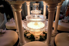 Table decoration of champagne fountain in light and wedding cake Royalty Free Stock Photography