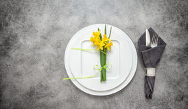 Table decoration cutlery, napkin, narcissus flowers Stock Images