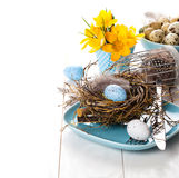 Table decoration with easter eggs nest on plate Stock Photography