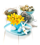 Table decoration with easter eggs nest on plate Royalty Free Stock Images