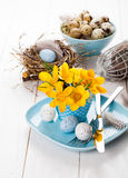 Table decoration with easter eggs nest on plate Royalty Free Stock Image