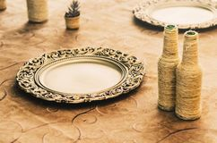 Table decoration with golden sousplat, some handcrafted bottles. And ornaments over the table Royalty Free Stock Photo