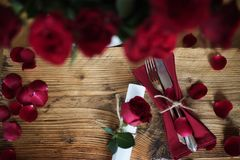 Table decoration for a romantic dinner. Table decoration with red roses for a romantic dinner on valentines day Royalty Free Stock Image