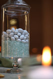 Table decoration with stone candies and candle Stock Photos