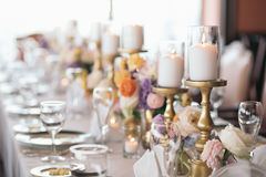 Table Decorations. Lit Candles. Flowers. Lit candles and colorful flowers decorate a dinner table Stock Photo