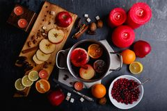 On the table is pan with mulled, a board with slices of apples and lemon, a plate with cranberries and candles. royalty free stock images