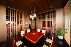 Table in deepening of floor in empty restaurant. Small square table in deepening of floor and chairs in empty stylish restaurant royalty free stock photo
