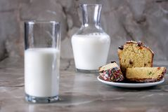 Delicious aromatic cake and a glass of milk on a table with a marbled background. stock image