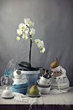 Table with dishes and white orchid Royalty Free Stock Photography