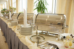 Table with dishware and shiny marmites Stock Photos