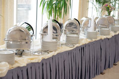 Table with dishware and shiny marmites Stock Images