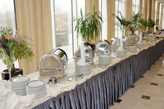 Table with dishware and shiny marmites Royalty Free Stock Photos