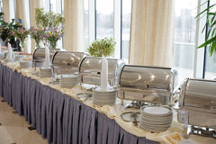 Table with dishware and shiny marmites Stock Photography