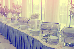 Table with dishware and shiny marmites, toned. Table with dishware and shiny marmites waiting for guests, toned image Royalty Free Stock Photos