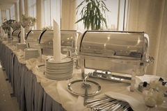 Table with dishware and shiny marmites Royalty Free Stock Images