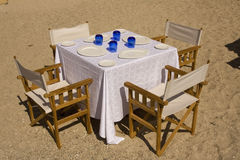 Table dressed on the beach. Table dressed for four on the beach, with white plates and blue glasses Royalty Free Stock Photography