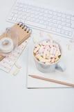 Table du bureau de la femme avec du café et des guimauves Images stock