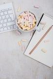 Table du bureau de la femme avec du café et des guimauves Photographie stock