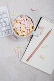 Table du bureau de la femme avec du café et des guimauves Photo stock