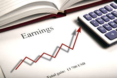 Table with earnings with digits, calculator and diagram. Close up Royalty Free Stock Images