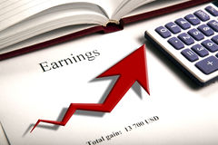 Table with earnings with digits, calculator and diagram. Close up Stock Photos