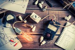 Table with electrical diagrams, a light bulb and books. Retro style royalty free stock photography