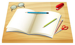 A table with an empty notebook, pencils, stapler and a scissor Stock Photo