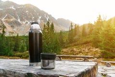 Table en bois avec des bancs sur une plate-forme en pierre parmi les montagnes Thermos avec la boisson chaude image libre de droits