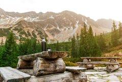Table en bois avec des bancs sur une plate-forme en pierre parmi les montagnes Thermos avec la boisson chaude photographie stock