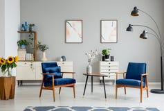 Table en bois avec des fleurs entre les fauteuils bleus dans l'intérieur plat gris avec des affiches photographie stock