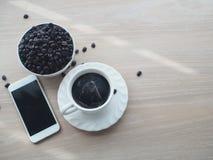 Table en bois avec du café noir chaud, le grain de café et l'écran vide o Images stock