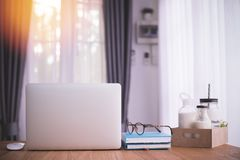 Table en bois avec l'ordinateur portable, le papier de carnet et beaucoup de lait sur le carton de boîte dans le salon images libres de droits