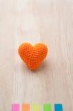 Table en bois avec la forme tricotée de coeur de tissus et le bâton coloré Photo stock