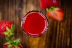 Table en bois avec la liqueur de fraise, foyer sélectif photographie stock