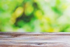 Table en bois avec le fond brouillé de jardin Photographie stock