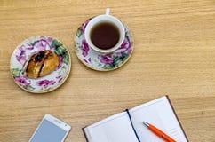 Table en bois avec le PC de table, le thé et les fournitures de bureau Image stock