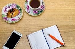 Table en bois avec le PC de table, le thé et les fournitures de bureau, Photos stock
