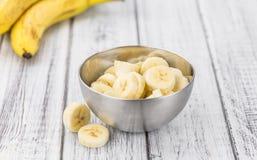 Table en bois avec les bananes coupées en tranches, foyer sélectif Photos libres de droits