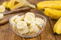 Table en bois avec les bananes coupées en tranches, foyer sélectif Images stock