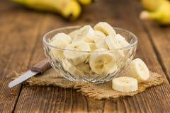 Table en bois avec les bananes coupées en tranches, foyer sélectif Image libre de droits