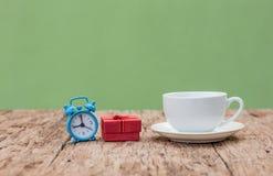 Table en bois avec une tasse de café en céramique, le boîte-cadeau et la montre Image stock