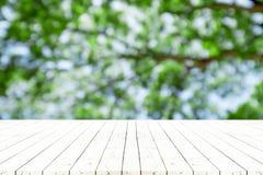 Table en bois blanche de perspective sur le dessus au-dessus du backgrou naturel de tache floue Image stock