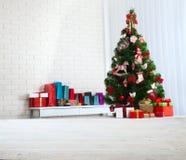 Table en bois blanche devant l'arbre de Noël coloré avec des boîte-cadeau peuvent être employés pour l'affichage ou le montage vo Photos libres de droits