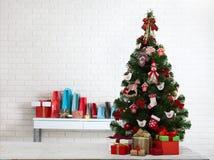 Table en bois blanche devant l'arbre de Noël coloré avec des boîte-cadeau peuvent être employés pour l'affichage ou le montage vo Photo libre de droits