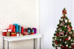 Table en bois blanche devant l'arbre de Noël coloré avec des boîte-cadeau peuvent être employés pour l'affichage ou le montage vo Photographie stock