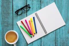 Table en bois bleue de bureau avec le carnet, le stylo de couleur, lunettes et Image libre de droits