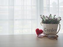Table en bois de bureau avec la fleur de rose de rose sur le pot, forme rouge de coeur Images stock