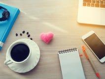 Table en bois de bureau avec la tasse de café chaude, écran vide sur le carnet Photos stock