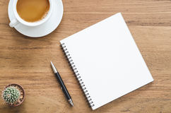 Table en bois de bureau avec le carnet, le stylo, le cactus et la tasse de café Photographie stock